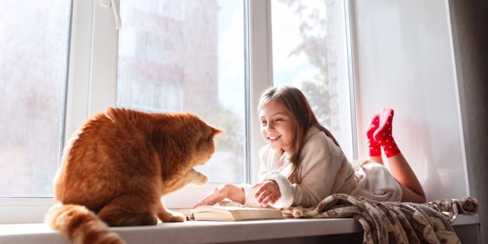 Child in warm terry robe lying on window sill and reading a book. Winter weekend with red cat at home.